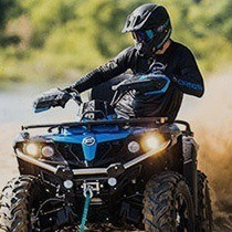 Man in a dark helmet rides a blue ATV.