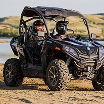 A couple sits in a UTV in a muddy river setting.