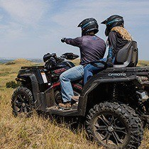 A man sits on an ATV and points into the distance while a woman sits behind him.