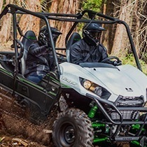 A couple in a green and white UTV speeds through muddy terrain.